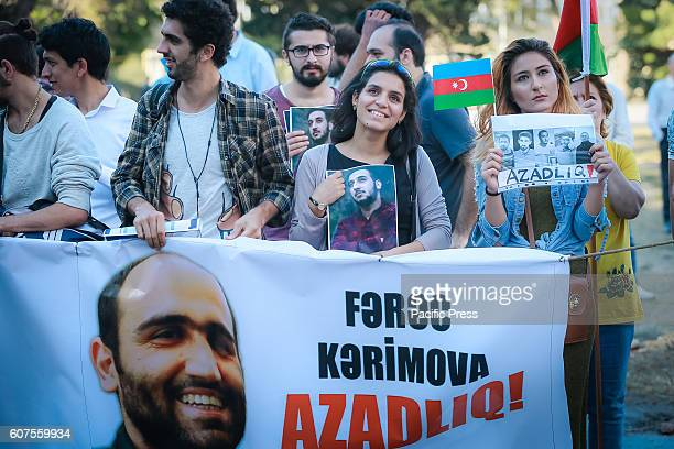 Azerbaijani opposition supporters holds palacards during the protest at Mahsul stadium Azerbaijan