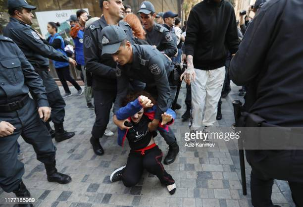 Azerbaijani police officers detain woman activist protesting against domestic violence and violence against women in Baku on October 20 2019 in Baku...