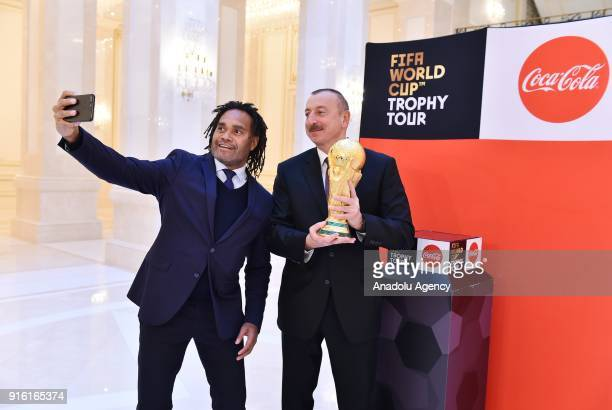 Azerbaijani President Ilham Aliyev holds the World Cup trophy as he poses for a photo with former French football player Christian Karembeu within...