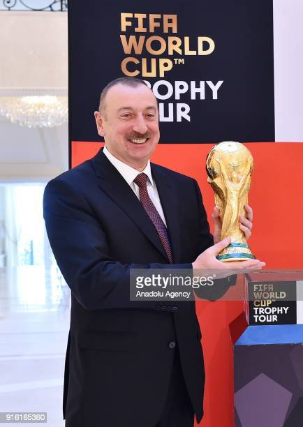 Azerbaijani President Ilham Aliyev poses for a photo as he holds the World Cup trophy within the FIFA World Cup Trophy Tour in Baku Azerbaijan on...