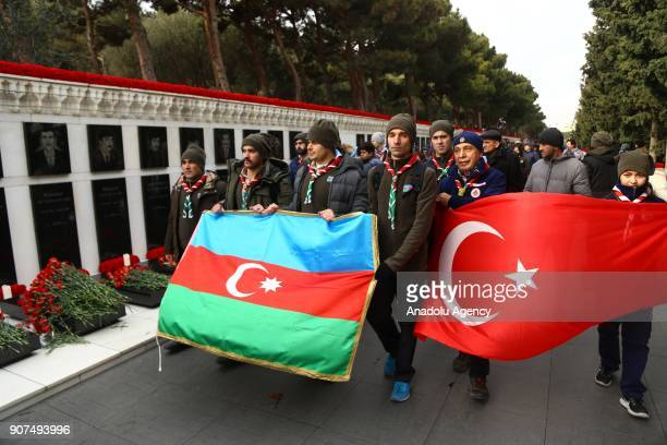 Azerbaijanis hold Azerbaijani and Turkish flags as they visit the Alley of Martyrs a cemetery and memorial dedicated to those killed by Soviet troops...