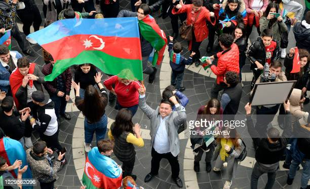 Azerbaijanis wave the national flag as they celebrate in the streets of the capital Baku on November 10 after Armenia and Azerbaijan agreed a...