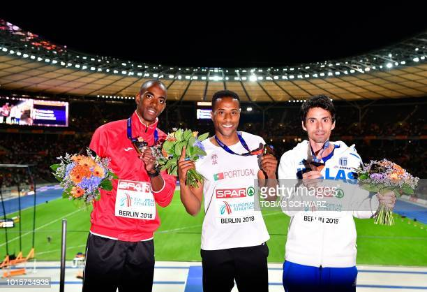 Azerbaijan's Alexis Copello Portugal's Nelson Evora and Greece's Dimitrios Tsiamis celebrate on the podium during the medal ceremony for the men's...