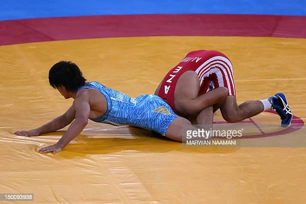 Azerbaijan's Ashraf Aliyev wrestles Japan's Sohsuke Takatani in their Men's 74kg Freestyle qualification match on August 10 2012 during the wrestling...