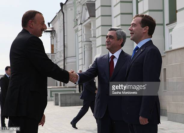 Azerbaijan's President Ilham Aliyev shakes hands with Armenian President Serge Sargsyan as Russian President Dmitry Medvedev looks on during their...