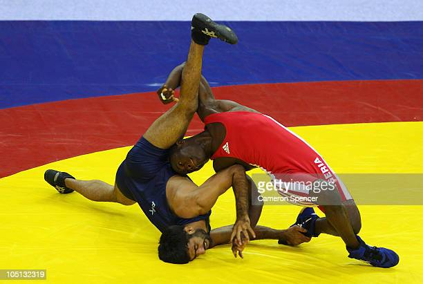 Azhar Hussain of Pakistan competes against Ebikewenimo Welson of Nigeria in the men's 55kg freestyle gold medal wrestling at IG Sports Complex during...