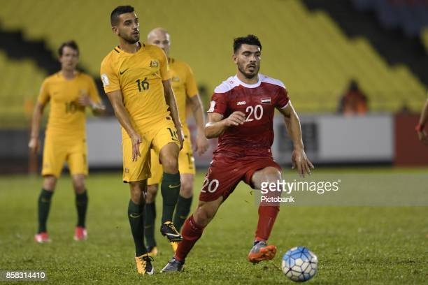 Aziz Behich of Australia challenges Khaled Almbayed of Syria for the ball during the FIFA 2018 World Cup Asian Playoff Leg 1 match between Syria and...