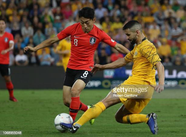Aziz Behich of Australia is pressured by Lee Jinhyun of Korea Republic during the International Friendly match between the Australian Socceroos and...