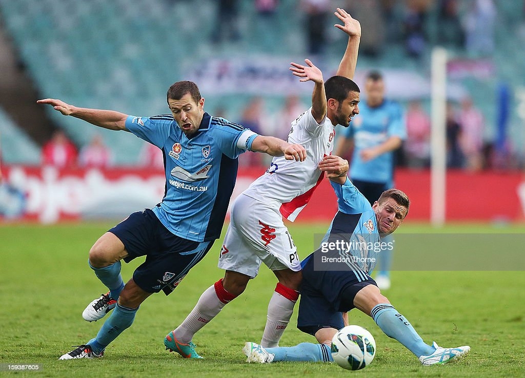 Aziz Behich of the Heart competes with Brett Emerton and Jason Culina of Sydney during the round 16 A-League match between Sydney FC and the Melbourne Heart at Allianz Stadium on January 13, 2013 in Sydney, Australia.