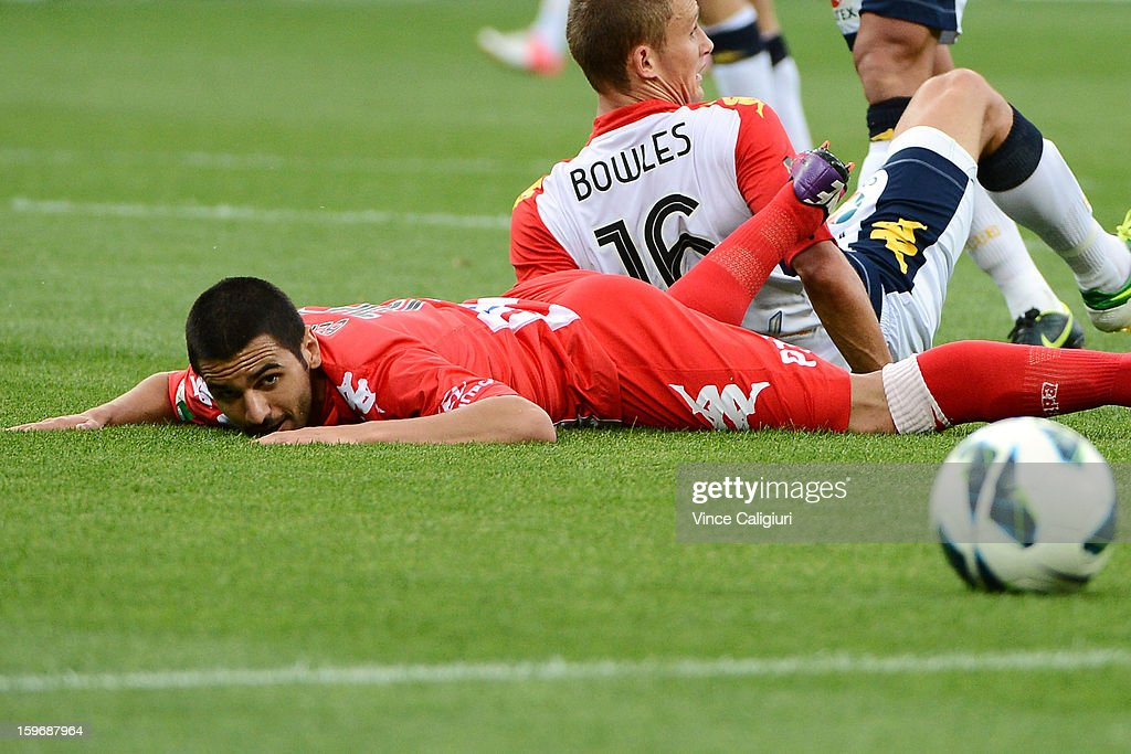 Aziz Behich of the Heart is tackled by Daniel Bowles during the round seventeen A-League match between Melbourne Heart and Adelaide United at AAMI Park on January 18, 2013 in Melbourne, Australia.