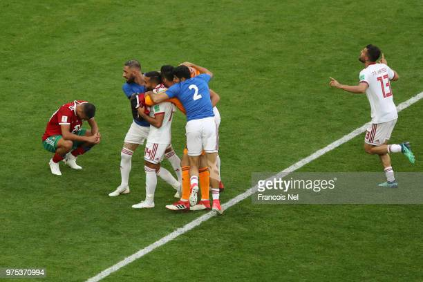 Aziz Bouhaddouz of Morocco looks dejected after scoring an own goal Iran's first as Iran players celebrate during the 2018 FIFA World Cup Russia...