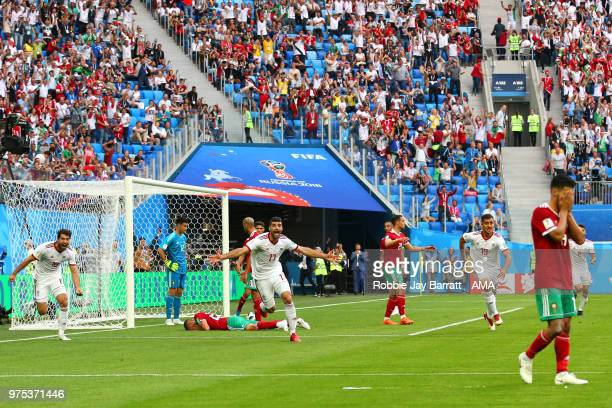 Aziz Bouhaddouz of Morocco reacts after scoring an own goal to make it 0-1 as Mohammad Reza Khanzadeh of IR Iran celebrates during the 2018 FIFA...