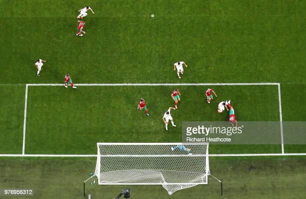 Aziz Bouhaddouz of Morocco scores an own goal for Iran's first goal, as Majid Hosseini, Mehdi Taremi, and Karim Ansarifard of Iran celebrate during...