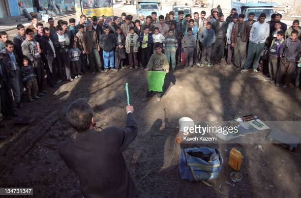 Aziz the village magician, with his makeshift bag of tricks spread in front of him, performs his tricks for a crowd in the town of Harris in...
