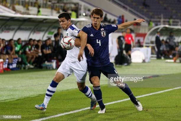 Azizbek Turgunbaev of Uzbekistan and Sho Sasaki of Japan compete for the ball during the AFC Asian Cup Group F match between Japan and Uzbekistan at...