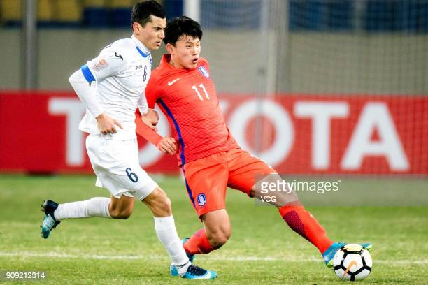 Azizjon Ganiev of Uzbekistan and Cho YoungWook of South Korea compete for the ball during the AFC U23 Championship semifinal match between Uzbekistan...