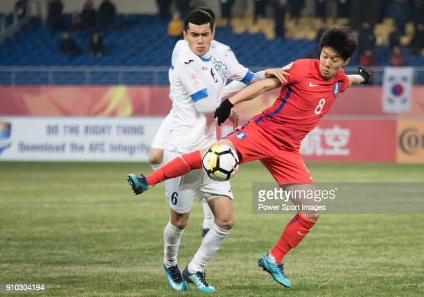 Azizjon Ganiev of Uzbekistan fights for the ball with Han SeungGyu of South Korea during the AFC U23 Championship China 2018 Semifinals match between...