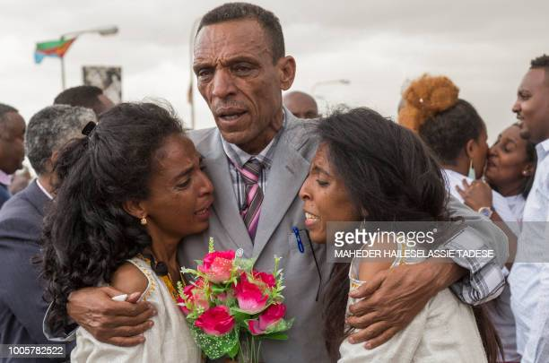 Azmera Addisalem and Danait Addisalem cry and hug their father an Ethiopian journalist at Asmara International airport on July 21 as they are...