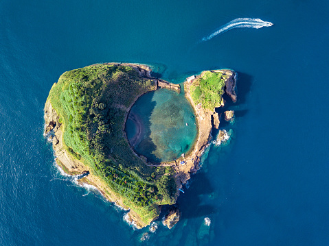 Azores aerial panoramic view. Top view of Islet of Vila Franca do Campo. Crater of an old underwater volcano. San Miguel island, Azores, Portugal. Heart carved by nature. Bird eye view. 1162800176