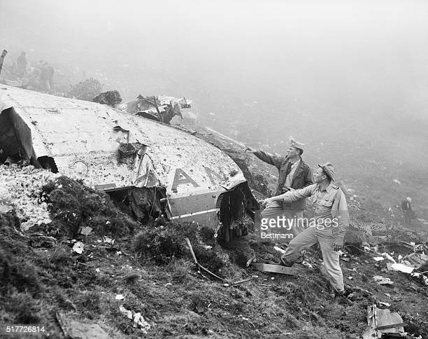 Two US Air Force officers from the USAF base at Lajes are shown examining wreckage of the Air France Constellation that crashed on an Azores mountain...