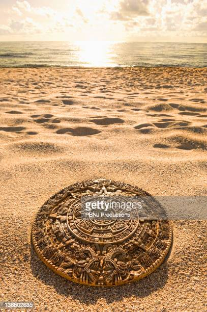aztec calendar stone carving on sandy beach - antiquities stock pictures, royalty-free photos & images