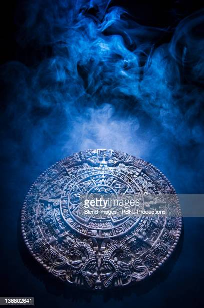 aztec calendar stone carving surrounded by smoke - aztec civilization stock photos and pictures