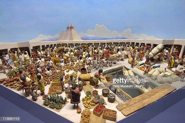 Aztec Market diorama at Tlatelolco Mexico AD 1515 busy marketplace with pyramid in background man unloading produce from a dugout canals connected...
