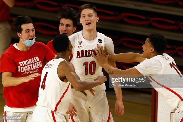 Azuolas Tubelis of the Arizona Wildcats celebrates with teammates Dalen Terry and Ira Lee after scoring against the Arizona State Sun Devils during...