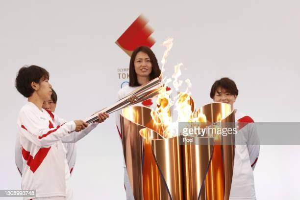 Azusa Iwashimizu , member of Japan women's football national team, lights the torch from the celebration cauldron during the Tokyo 2020 Olympic Torch...