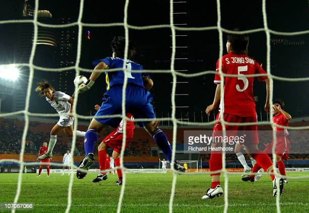 Azusa Iwashimizu of Japan heads the ball into the net for the game-winning goal past goalkeeper Myong Hui Hong of North Korea during the women's gold...