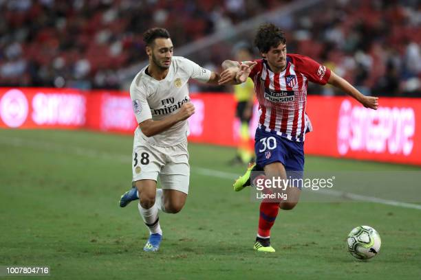Azzedine Toufiqui of Paris Saint Germain and Roberto Olabe of Atletico Madrid chase after the ball during the International Champions Cup match...