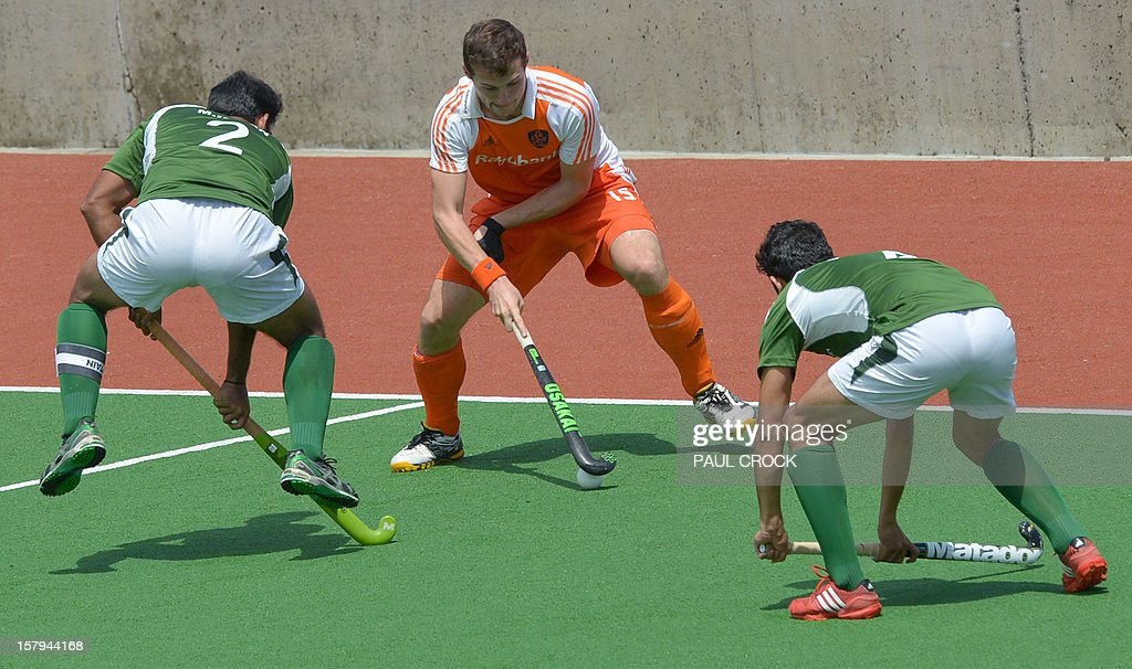 Baart Sander of The Netherlands (C) fights through defenders Captain Muhammad Imran (L) and Muhammad Rizwan Jnr (R) of Pakistan during their semi final match at the Men's Hockey Champions Trophy in Melbourne on December 8, 2012. IMAGE STRICTLY RESTRICTED TO EDITORIAL USE - STRICTLY NO COMMERCIAL USE AFP PHOTO/Paul CROCK