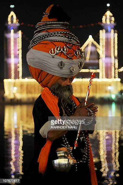 Baba 'Avtar' Singh a member of the traditional Sikh religious warriors' Nihang Army clad in a 300 meterlong turban pays his respects at the...