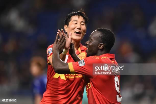 Baba Diawara of Adelaide United celebrates scoring a goal with Jaesung Kim during the AFC Champions League Group H match between Gamba Osaka v...