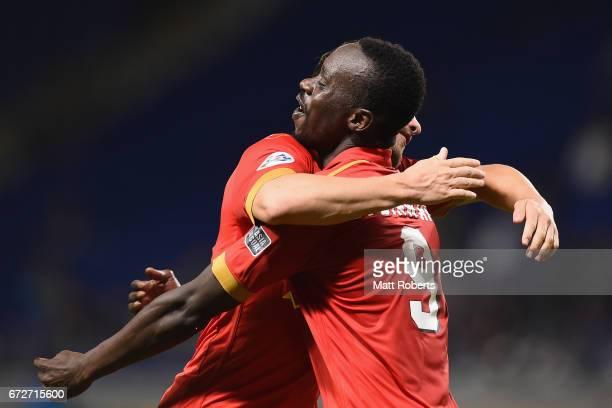 Baba Diawara of Adelaide United celebrates scoring a goal with team mates during the AFC Champions League Group H match between Gamba Osaka v...