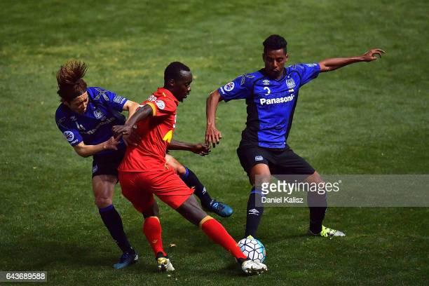 Baba Diawara of United competes for the ball with Fujiharu Hiroki and Niwa Daiki of Gamba Osaka during the AFC Asian Champions League match between...