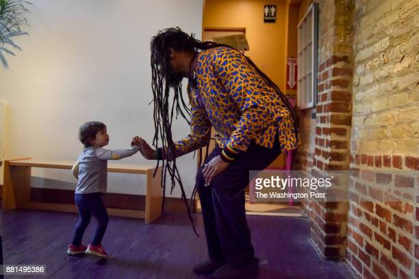 Baba Ras D the premiere child entertainer in DC these days greets a child who has been brought to see his performance at BloomBars on Thursday...