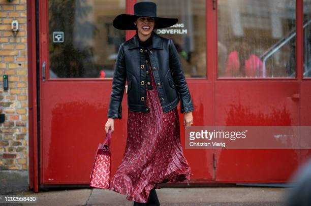 Baba Rivera is seen wearing oversized hat, black leater jacket, Coach bag and red dress outside Rave Review on Day 1 during Copenhagen Fashion Week...