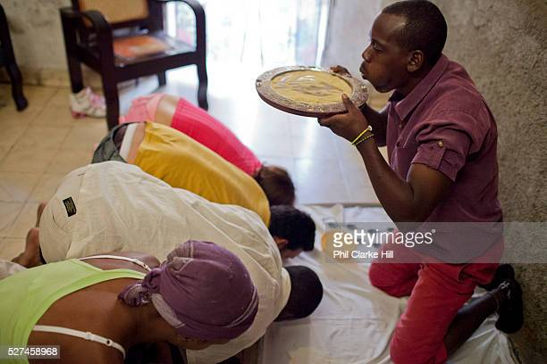 Babalawo using cowry shells and corn powder to read the fortunes of the people being initiated Santeria is a syncretic religion practiced in Cuba it...