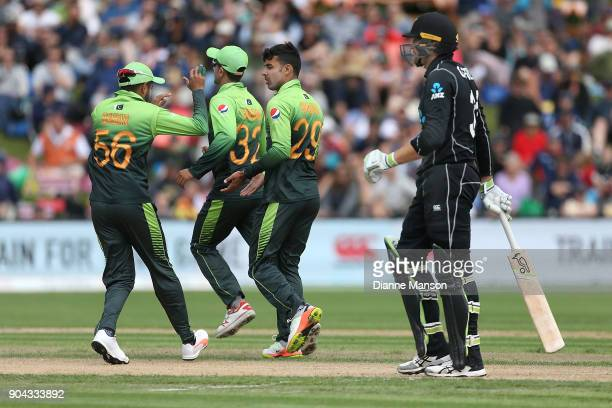 Babar Azam Hassan Ali and Shadab Khan of Pakistan celebrate the dismissal of Martin Guptill of New Zealand during the third game of the One Day...