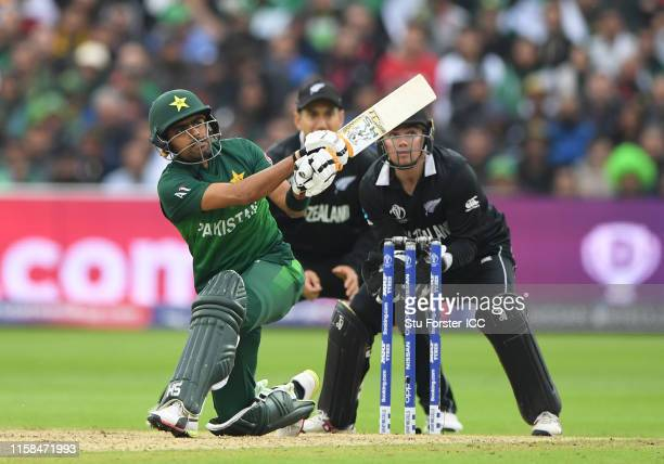 Babar Azam of Pakistan plays a shot for four as Ross Taylor and Tom Latham of New Zealand look on during the Group Stage match of the ICC Cricket...