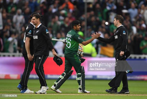 Babar Azam of Pakistan shakes hands with members of the New Zealand side after his sides victory during the Group Stage match of the ICC Cricket...