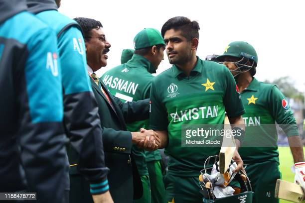 Babar Azam of Pakistan undefeated on 101 runs is congratulated by team and staff after Pakistan's six wicket win during the Group Stage match of the...