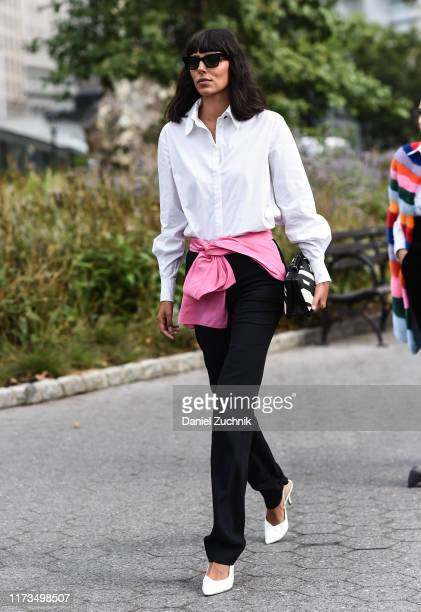 Babba Rivera is seen wearing a white shirt, pink sweater, black pants and white heels with sunglasses outside the Carolina Herrera show during New...