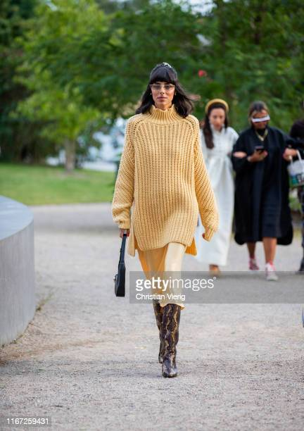 Babba Rivera is seen wearing yellow oversized knit, silk dress, boots with snake print outside Samsøe & Samsøe during Copenhagen Fashion Week...
