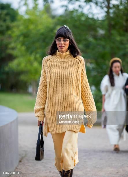 Babba Rivera is seen wearing yellow oversized knit, silk dress, boots with snake print outside Samsøe & Samsøe during Copenhagen Fashion Week...
