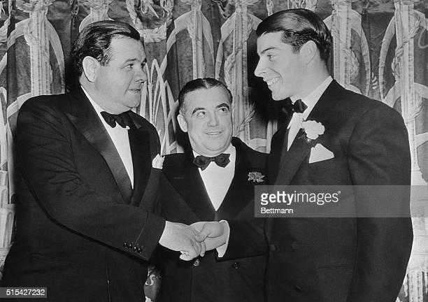 Babe Ruth, former baseball Great, who starred for the New York Yankees, , shakes hands here with Joe DiMaggio, hard hitting outfielder of the present...