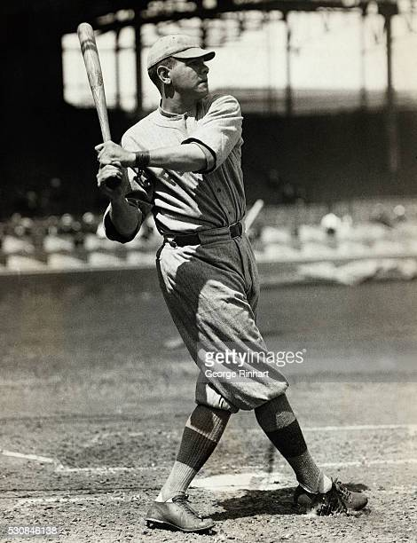 Babe Ruth is shown at the end of swinging his bat while playing baseball with the Boston Red Sox.