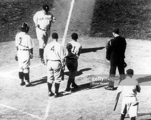 Babe Ruth of the New York Yankees scores after hitting a threerun homerun in the first inning as he is congratulated by teammates Joe Sewell who...