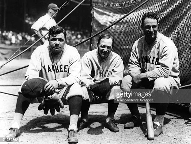 Babe Ruth outfielder Miller Huggins manager and Lou Gehrig first baseman all of the New York Yankees take a break at the batting cage before a game...